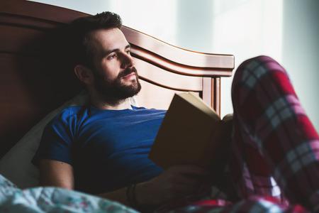 Giovane che legge un libro nella sua camera da letto