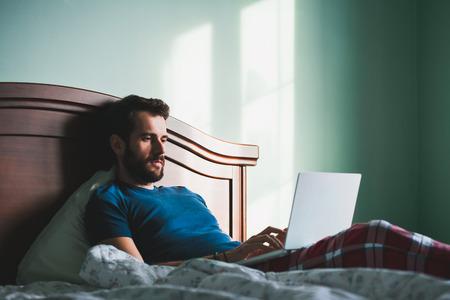 노트북에서 작업 침대에 누워있는 젊은 남자 스톡 콘텐츠