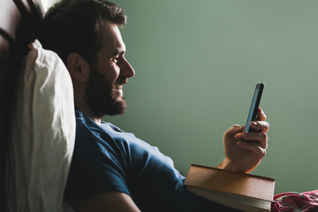 Young man lying in the bed with a book in his lap and a smartphone in his hand Stock Photo