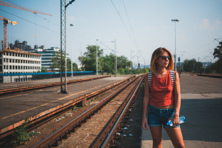 Young female backpacker waiting for the train Stock Photo