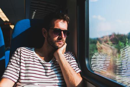 Giovane uomo che viaggia su un treno seduto vicino alla finestra