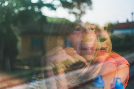 창을 통해 찾고 기차로 여행하는 젊은 여자의 창에 반영