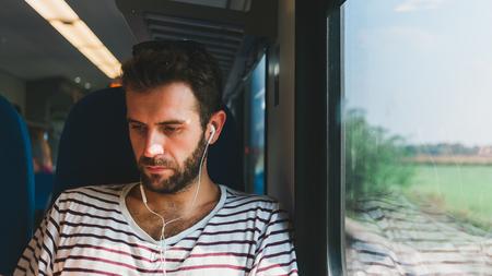 Giovane uomo che viaggia su un treno seduto vicino alla finestra ad ascoltare la musica