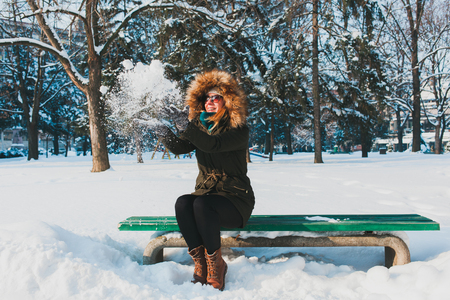 Young woman playing with snow in the park sitting on the bench