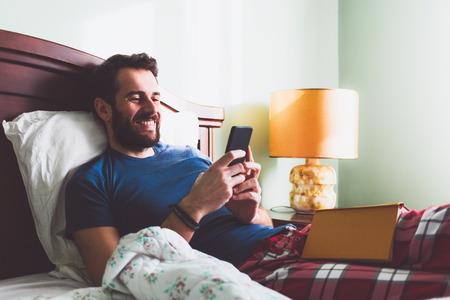 자신의 무릎에 책을 그의 손에 스마트 폰과 함께 침대에 누워있는 젊은 남자