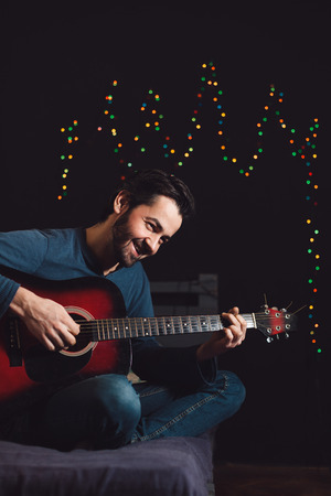 Young man playing guitar and composing a song Stock Photo