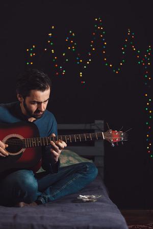 Giovane uomo a suonare la chitarra e comporre una canzone Archivio Fotografico