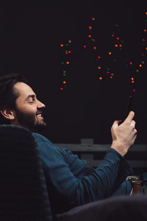 행복 한 젊은 남자가 소파에 편안하고 핸드폰 사용