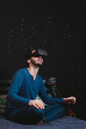 Giovane uomo con gli occhiali di realtà virtuale e seduto sul divano in una stanza