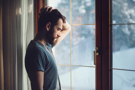 Young sad mad sitting by the window in regret Stock Photo