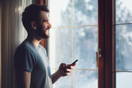 Giovane uomo con la barba in piedi accanto alla finestra utilizzando uno smartphone Archivio Fotografico