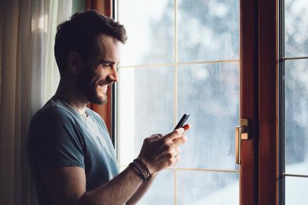 스마트 폰을 사용하여 창에 의해 서 젊은 수염 남자