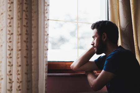 Giovane triste pazza seduto vicino alla finestra nel rimpianto