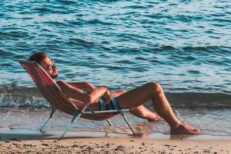 Giovane uomo bello prendere il sole sulla spiaggia