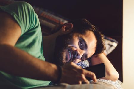 밤에 자신의 침대에서 스마트 폰을 사용하는 젊은 남자