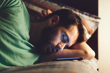 Giovane che usando uno smartphone nel suo letto di notte