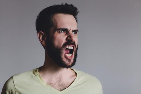 부정적인 감정을 보여주는 젊은 수염 남자, 스튜디오 촬영. 스톡 콘텐츠