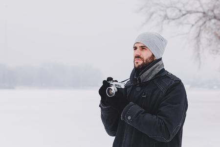 겨울 시간에 얼어 붙은 호수에 사진을 복용하는 젊은 남자