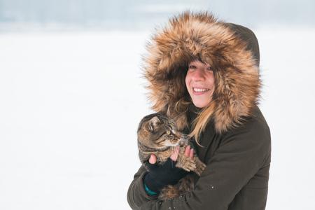 고양이를 들고 겨울에 외부 젊은 여자
