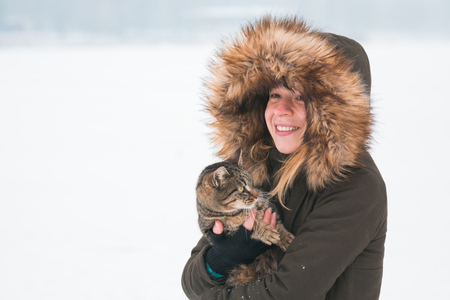 Young woman outside in the winter holding a cat