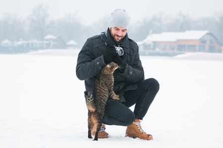 Cat cuddling with photographer outside in the snow