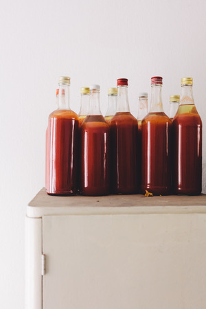 Bottles of fresh homemade strawberry juice on the cabinet