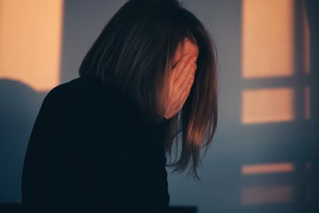 Una donna seduta da sola e depressa nella luce della finestra Archivio Fotografico