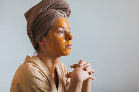 Giovane donna con una maschera di uovo sul viso