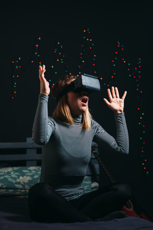 Young woman wearing virtual reality glasses and sitting on sofa in a room 스톡 콘텐츠