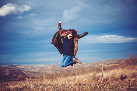 Young successful woman jump on mountain top