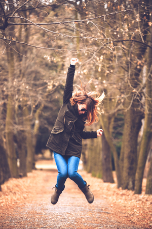 Young successful woman jump in the park