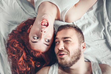 Top view of a happy couple heads to each other on white bed sheets