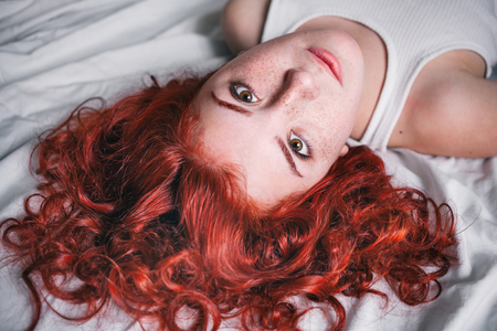 Portrait of young beautiful woman with long hair lying in the bed 스톡 콘텐츠