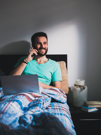 Young man lying on the bed talking on a smartphone with a laptop in his lap