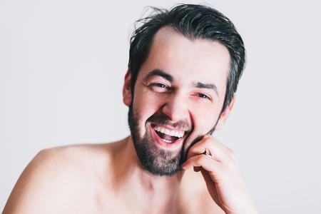 Young bearded man laughing, studio shot. Archivio Fotografico