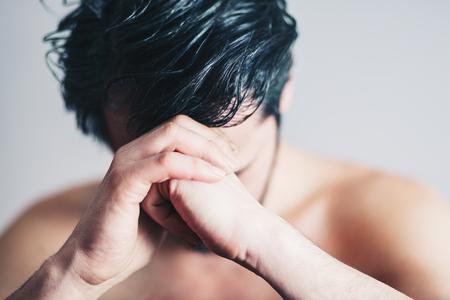 Young man in pain praying