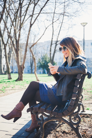 Young woman sitting on the bench in the park using smartphone