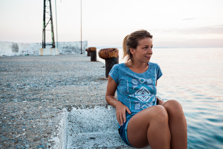 Young woman sitting on the pier by the sea