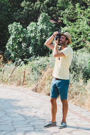 Young man taking a photograph in a countryside