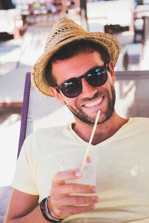 Young smiling man drinking lemonade in a cafe