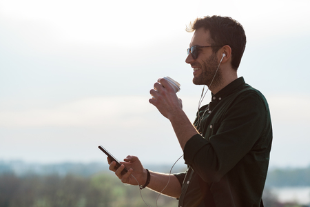 Young man drinking coffee listening to the music on the smartphone