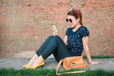 Young woman sitting in the park using smartphone