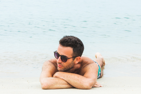 Handsome young man sunbathing on the beach