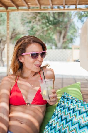 Young woman drinking lemonade in a beach bar