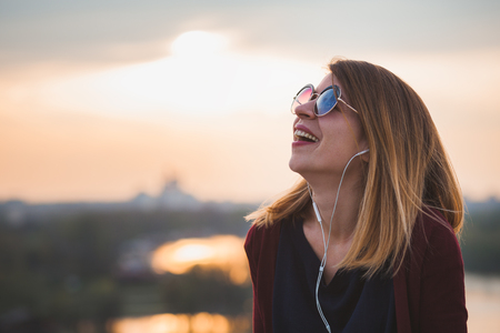Young woman enjoying outdoors listening to the music