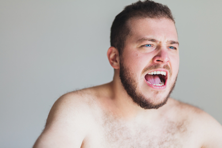 Young emotional man screaming in anger