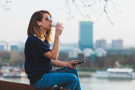 Young woman enjoying  coffee break listening to the music