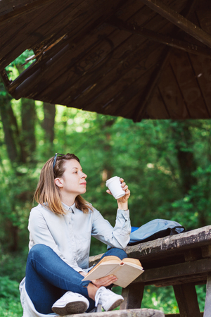 Young woman enjoying coffee and reading book in the park