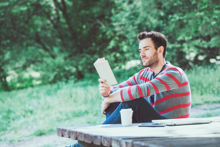 Young man reading a book in the park