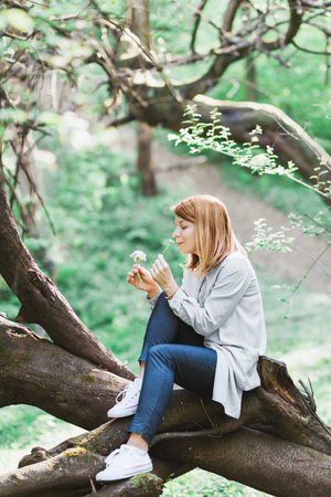 Young woman smelling flowers outside in nature